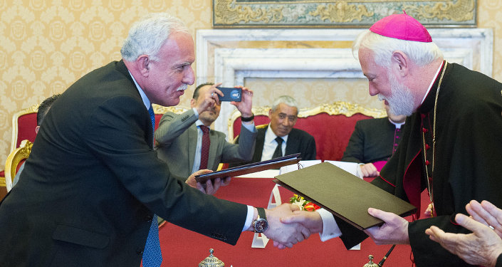Vatican Foreign Minister Paul Gallagher, right, and his Palestinian counterpart, Riad al-Malki, shake hands after signing a treaty at a ceremony inside the Vatican, Friday, June 26, 2015