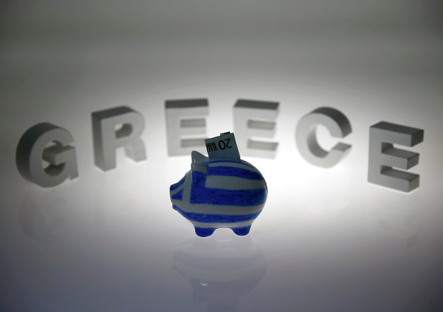 A piggybank painted in the colours of the Greek flag with a 20 euro banknote in it's slot, stands in front of letters spelling the word 'GREECE' in this picture illustration taken in Berlin, Germany June 30, 2015