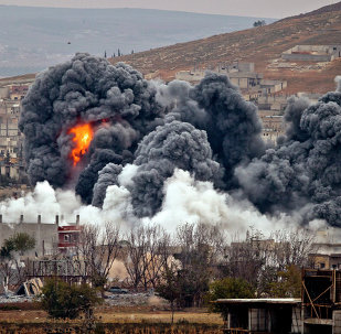 Smoke rises from the Syrian city of Kobani, following an airstrike by the US led coalition, seen from a hilltop outside Suruc, on the Turkey-Syria border Monday, Nov. 17, 2014.