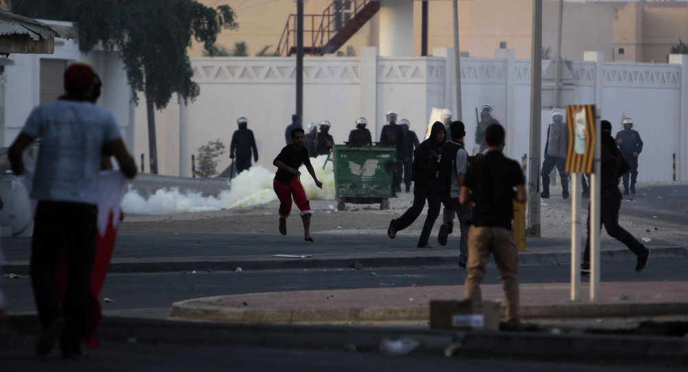 Bahraini anti-government protesters clash with riot police firing tear gas in front of a police station Saturday, Dec. 31, 2011, in the western Shiite Muslim village of Karzakan, Bahrain