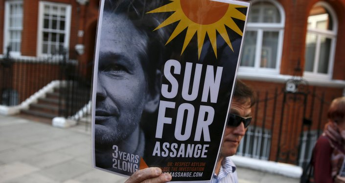 A supporter of Wikileaks founder Julian Assange holds a placard during a gathering outside the Ecuador embassy in London, Britain June 19, 2015