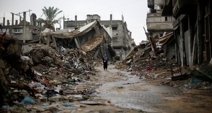 A Palestinian woman walks in the rain past houses that were destroyed during the 50-day Gaza war between Israel and Hamas-led militants, on November 24, 2014, in Gaza City