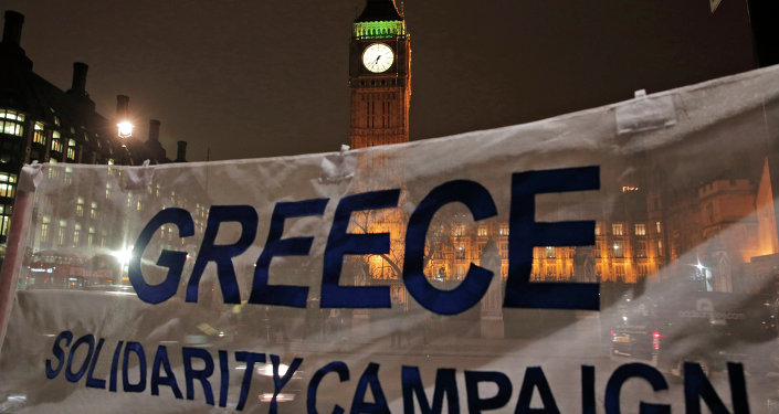 Backdropped by the Houses of Parliament in central London, protesters hold a banner at a rally to show solidarity with Greece. File photo