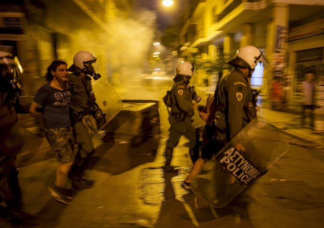 Riot police detain a youth during minor clashes in central Athens, Greece July 5, 2015