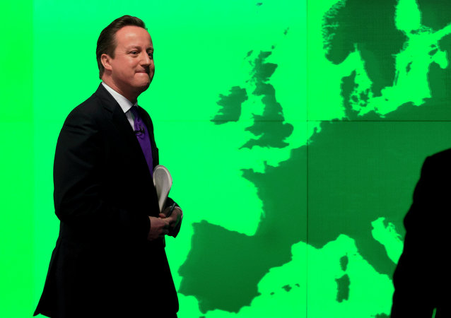 Britain's Prime Minister David Cameron walks past a map of Europe on a screen.