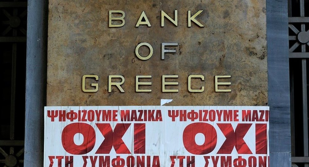 Posters reading We vote en masse, no the agreement'' are seen under a Bank of Greece sign in Athens, Friday, July 3, 2015.