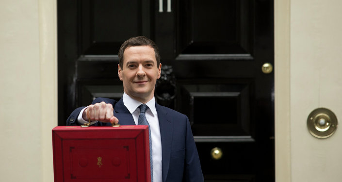 British Chancellor of the Exchequer George Osborne poses for the media with the traditional red dispatch box outside his official residence, 11 Downing Street in London, prior to unveiling the budget, Wednesday, July 8, 2015.
