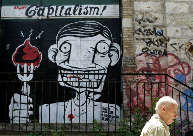 A man passes graffiti in Athens, Tuesday, July 7, 2015. Greek Prime Minister Alexis Tsipras was heading Tuesday to Brussels for an emergency meeting of eurozone leaders, where he will try to use a resounding referendum victory to eke out concessions from European creditors over a bailout for the crisis-ridden country