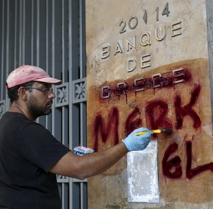 A worker cleans graffiti outside the central Bank of Greece building in Athens, Greece, July 7, 2015