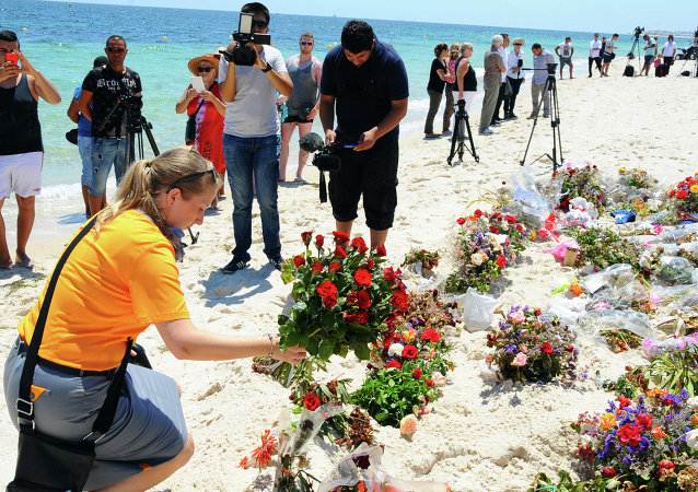 An unidentified tourist lays flowers to honor the victims of the June 26 terrorist attack in Tunisia.