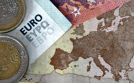 A picture taken on July 11, 2015 in Athens shows euro coins and banknotes with the map of Europe