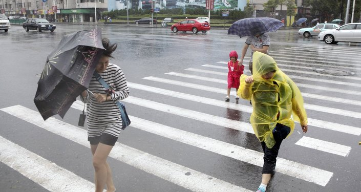 Pedestrians hold their umbrellas against strong wind China