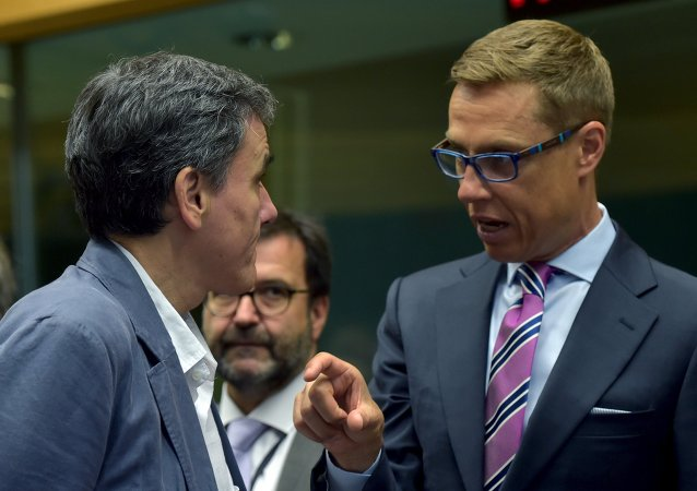 Greek Finance Minister Euclid Tsakalotos (L) chats Finland's Finance Minister Alexander Stubb during an euro zone finance ministers' meeting on the situation in Greece, in Brussels, Belgium, July 12, 2015
