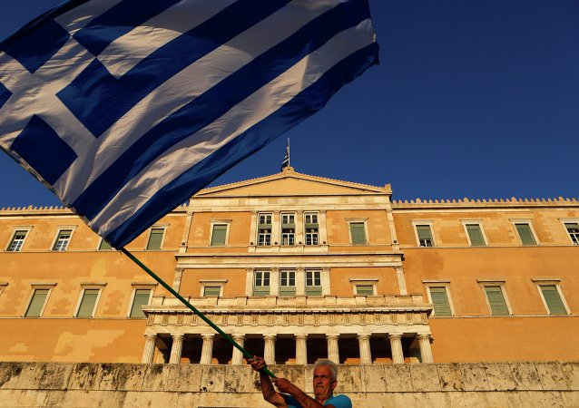A pro-Euro demonstrator waves a Greek flag in front of the Greek Parliament during a rally at Syntagma square in Athens, Thursday, July 9, 2015