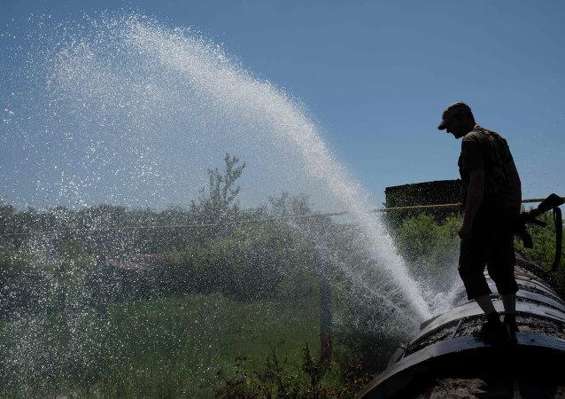 An Ukrainian soldier looks at a shelling damaged water pipeline in Dzerzhinsk, eastern Ukraine.
