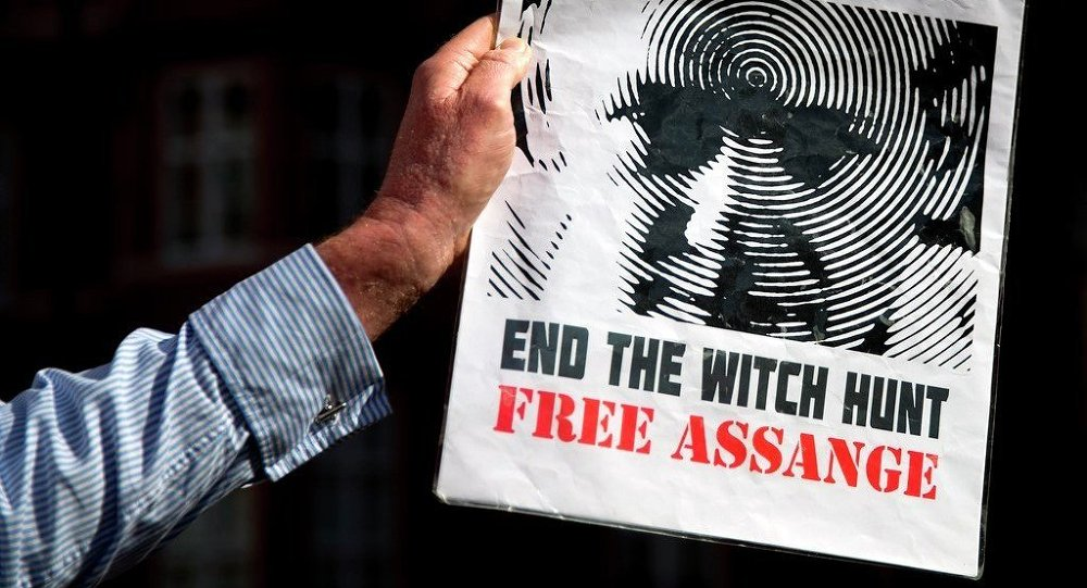 A supporter of Wikileaks founder Julian Assange holds a banner outside the Ecuadorian embassy in London.
