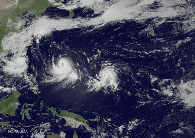 This satellite image taken by the JMA MTSAT-2 satellite at 6:30 a.m. EDT., on Tuesday, July 7, 2015 and released by the National Oceanic and Atmospheric Administration (NOAA), shows three storms in the North Pacific Ocean, from left, tropical storm Linfa, in the South China Sea meandering slowly northward, typhoon Chan-Hom with winds near 100 knots and strengthening, heading west-northwest toward the East China Sea, and typhoon Nangka, east of Guam heading west-northwest