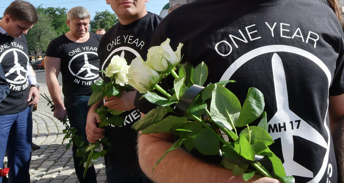 People wearing t-shirts bearing a drawing of a plane and slogans reading  MH 17, One year in the skies hold flowers to the Dutch embassy in Kiev on July 17, 2015 in memory of the people who died in the crash of Malaysian Airlines flight MH17
