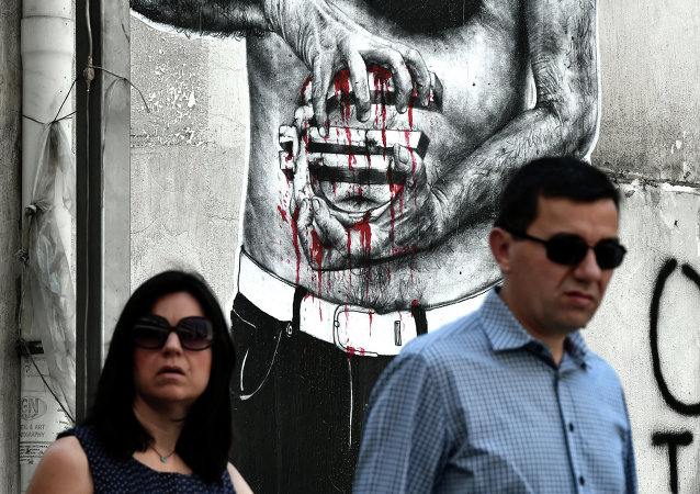 People pass by a graffiti showing a euro sign bleeding, in central Athens on July 14, 2015