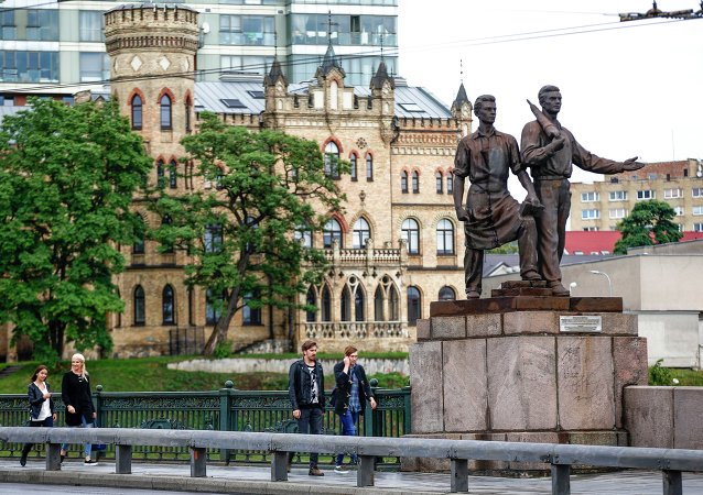 People walk past Soviet era statues at the Green Bridge over the Neris river in Vilnius, Lithuania, Monday, July 13, 2015