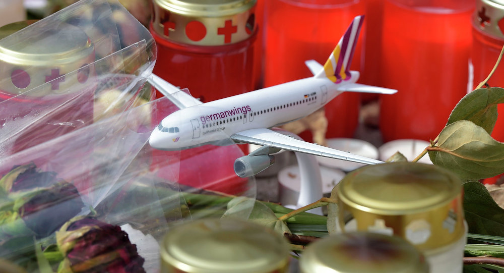A model of a plane is placed between candles and flowers in front of the Germanwings headquarters in Cologne, western Germany for the victims of the plane crash two weeks ago in the French Alps, Tuesday, April 7, 2015