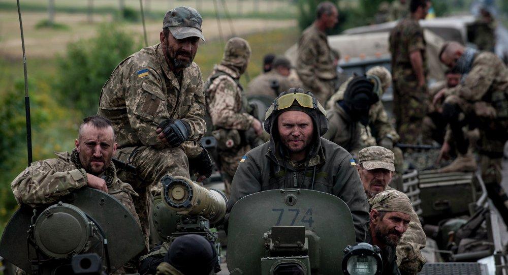 In this photo taken Tuesday, July 14, 2015, Ukrainian servicemen ride atop an armored vehicle near Krasnoarmiisk, Donetsk region, eastern Ukraine