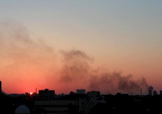 Black smoke billows in the sky amid clashes between rival Libyan factions in Benghazi.