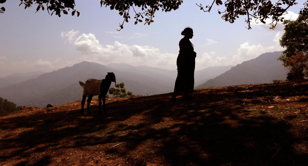 A woman waits for relief material at a Nepalese village