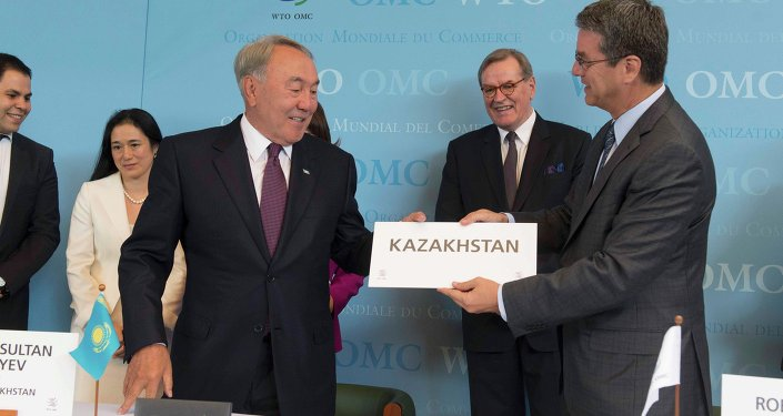 WTO Director general Roberto Azevedo (R) offers Kazakhstan's country sign to President Nursultan Nazarbayev after the accession ceremony at the World Trade Organization (WTO) headquarters in Geneva, Switzerland July 27, 2015