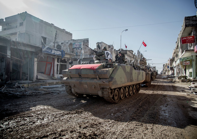 Turkish army vehicles drive in a street of the Syrian town of Kobane (aka Ain al-Arab) on February 22, 2015