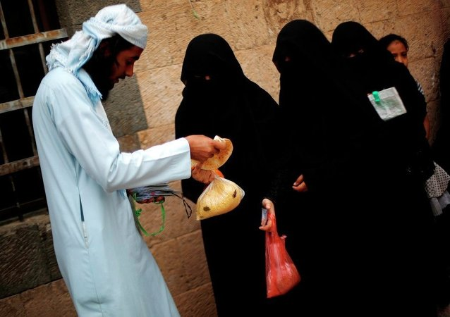 Yemeni women receive free food donated by Yemeni volunteers during the holy month of Ramadan, in Sanaa, Yemen, Friday, June 26, 2015.