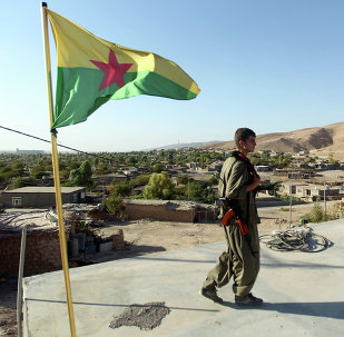 A Kurdistan Workers Party (PKK) fighters guards a post flying the PKK flag. File photo