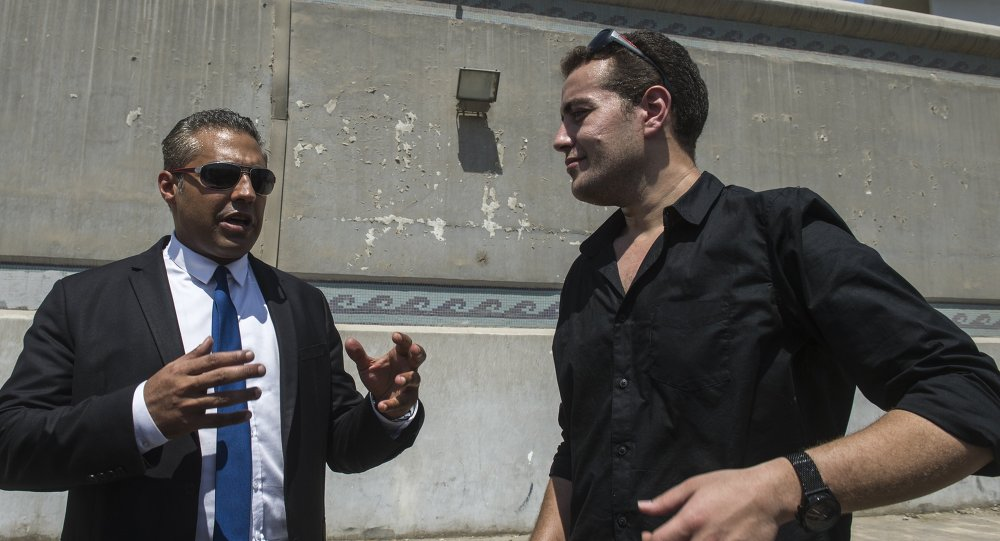 Former Al-Jazeera journalists, Canadian Mohamed Fahmy (L) and Egyptian Baher Mohamed, wait outside Cairo's Torah prison where their trial was due to take place on July 30, 2015.