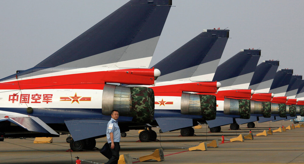 A man walks pasT the Chinese-made J-10 jet fighters on display at the 8th China International Aviation and Aerospace Exhibition (Zhuhai Airshow) in Zhuhai.