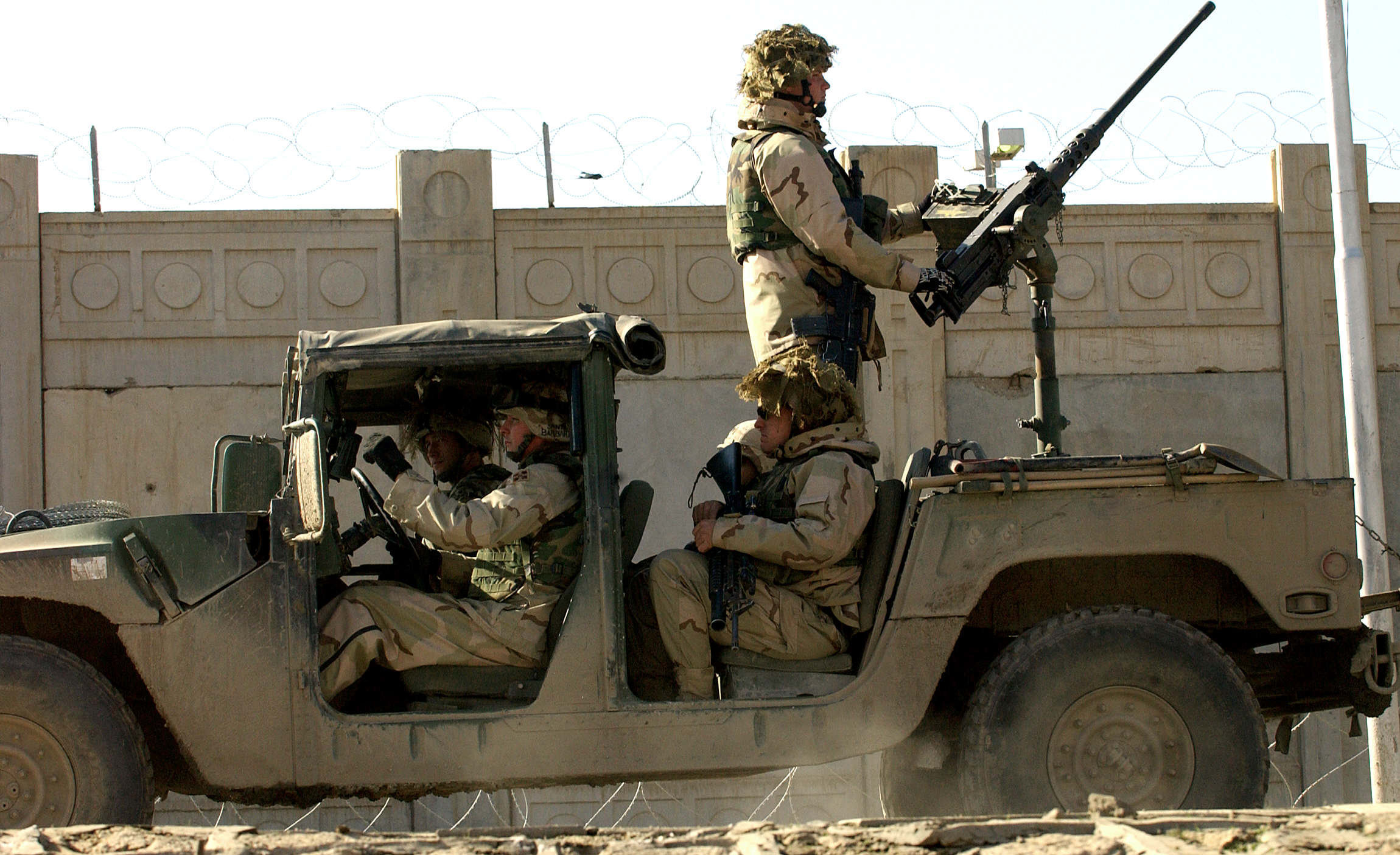 US soldiers from the 1st Battalion, 22nd Regiment of the 4th Infantry Division, ride on a military vehicle as they leave their base on a mission in Tikrit, 180 Kilometers (110 miles) north of Iraqi capital Baghdad, 30 December 2003.