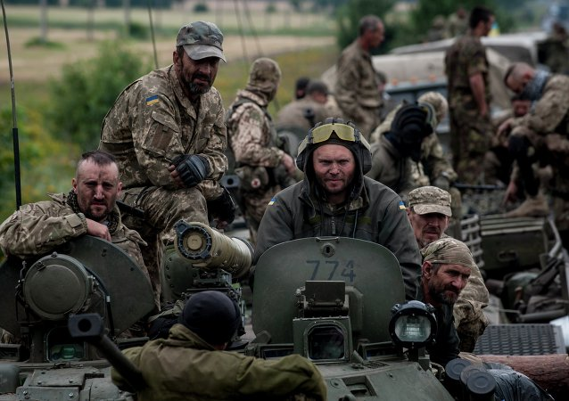 In this photo taken Tuesday, July 14, 2015, Ukrainian servicemen ride atop an armored vehicle near Krasnoarmiisk, Donetsk region, eastern Ukraine
