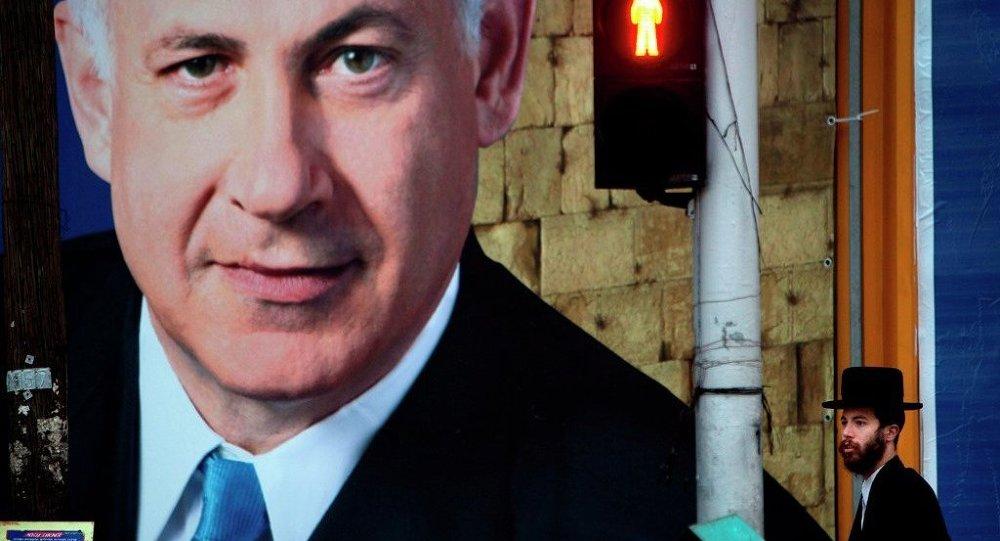 An Israeli ultra-orthodox Jewish man walks past an election campaign billboard of Israeli Prime Minister and Likud Party leader Benjamin Netanyahu, in Bnei Brak, near Tel Aviv, Israel, Sunday, Jan. 6, 2013.