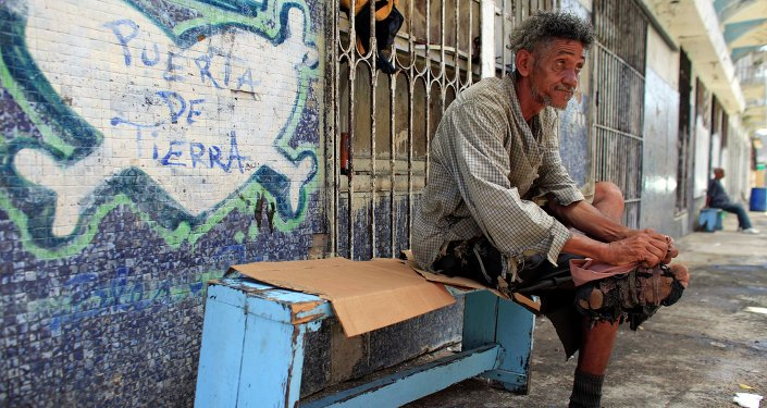 A homeless man improvises his shoes with pieces of cloth in front of a closed down business in Puerta de Tierra in the outskirts of Old San Juan, Puerto Rico, Sunday, Aug. 2, 2015