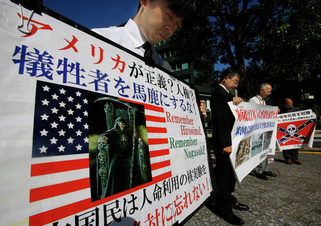 Member of a rightist group offer silent prayers for the victims of the atomic bombing with anti-US banners near the US Embassy in Tokyo, Thursday, Aug. 6, 2015.