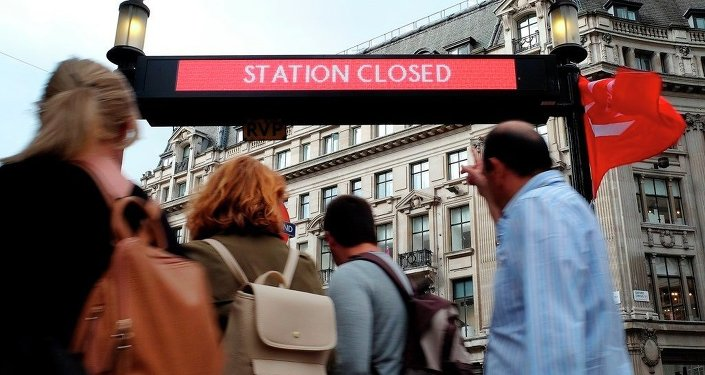 People pass the closed tube station entrance at Oxford Circus in London, Thursday, Aug. 6, 2015.