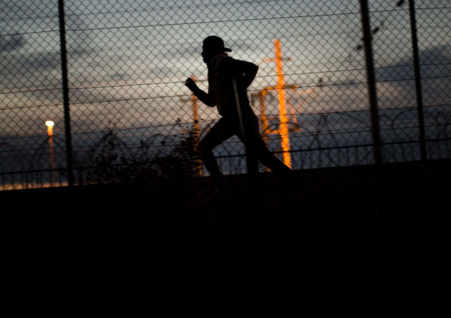 A migrant runs after crossing a fence as he attempts to access the Channel Tunnel, in Calais, northern France, Monday, Aug. 3, 2015.