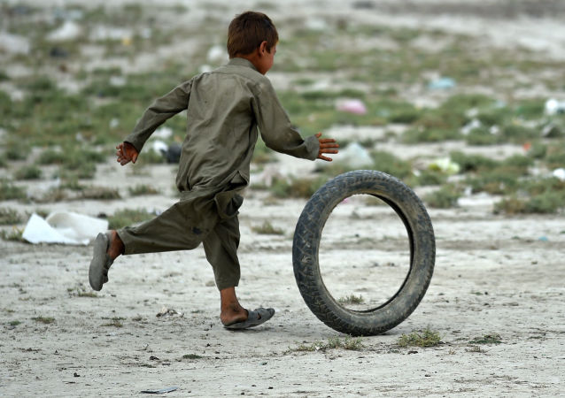 An Afghan Kochi nomad boy plays with a tire outside his tent on the outskirts of Kabul on August 2, 2015