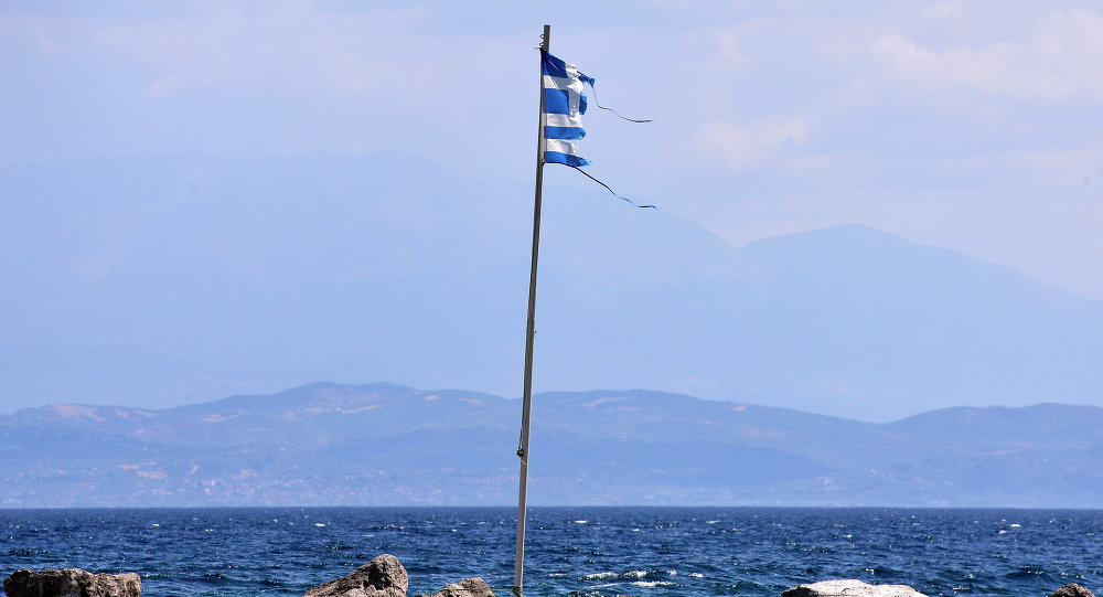 A torn Greek flag flutters at a coast near Antirio, southwest of Athens on August 9, 2015