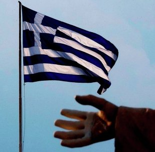 A hand of a statue is seen as the Greek flag waves in Athens, Sunday, June 28, 2015.