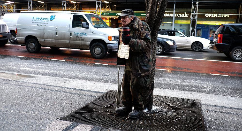 A homeless man begs for donations outside a subway station in New York on February 4, 2015