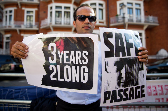 A supporter of Wikileaks founder Julian Assange holds banners outside the Ecuadorian embassy in London as he marks three years since Assange claimed asylum in the embassy on June 19, 2015.