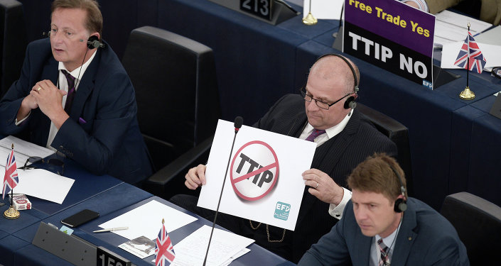 Members of the European Parliament take part in a voting session as they hold signs against the Transatlantic Trade and Investment Partnership (TTIP), on June 10, 2015, in the European Parliament in Strasbourg, eastern France