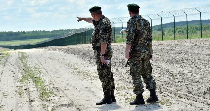 Ukrainian border guards patrol on July 2, 2015 along the barbed wire fence on the Senkivka border post, around 200 kilometres (125 miles) north of the Ukrainian capital Kiev.