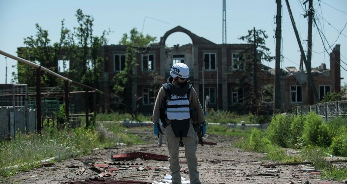 An OSCE monitor checks the territory for mines during a patrol in Shyrokyne, Donetsk region eastern Ukraine, Saturday, July 4, 2015