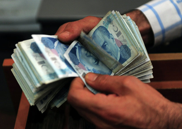 An exchange office worker counts Turkish lira banknotes in Istanbul on June 8, 2015